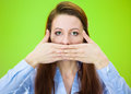 Speak no evil closeup portrait of young woman covering closed mouth open eyes concept isolated on green background negative human Stock Images