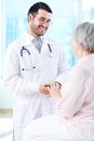 Speaking with patient confident doctor looking at his senior while to her Royalty Free Stock Photography