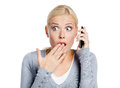 Speaking phone shocked girl covers her mouth hand isolated white Stock Photos