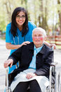 Special care facility for the elderly kind doctor nurse outdoors taking of an ill women in wheelchair Stock Photography