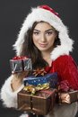 Special christmas times beautiful young woman dressed in santa costume carrying bunch of wrapped presents over dark background Royalty Free Stock Photo