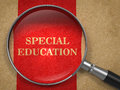 Special education magnifying glass concept on old paper with red vertical line background Royalty Free Stock Images
