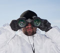 Special forces soldier in white camouflage looking through binoculars against blue sky Royalty Free Stock Images