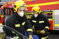 Specialist fire service officers prepare to break window order to cut collision victim free car following collision Stock Photo