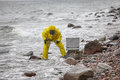 Specialist in protective suit taking sample of water to container on rocky shore Stock Images