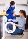 Specialist with tools and woman in uniform young women washing machine Stock Photos