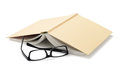 Spectacles beside inverted book on white background Stock Image