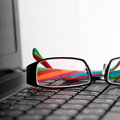 Spectacles on the keyboard closeup composition Stock Image