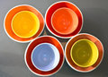 Spectacular colorful bowls inserted into one another four bright colored round porcelain bowl each other on the background of gray Royalty Free Stock Photo