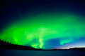 Spectacular display intense northern lights aurora borealis forming green swirls over single isolated illuminated house vast snowy Royalty Free Stock Photography