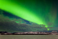 Spectacular display intense northern lights aurora borealis polar lights forming green band over snowy winter landscape lake Royalty Free Stock Photo