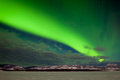 Spectacular display intense northern lights aurora borealis polar lights forming green band over snowy winter landscape lake Royalty Free Stock Images