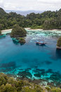 Spectacular tropical lagoon a wooden yacht sits in the midst of a in raja ampat indonesia this part of the pacific contains a Stock Images