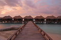 Spectacular twilight in tropical island connected with wooden walkway silky water and luxury overwater bungalow on Stock Photography
