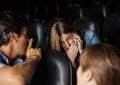 Spectator giving shh expression to woman using male women mobilephone in movie theater Stock Photo