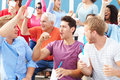 Spectators cheering at outdoor sports event smiling Stock Images
