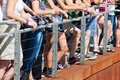 Spectators standing at a handrail along Stock Images