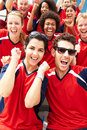 Spectators in team colors watching sports event cheering Royalty Free Stock Photos