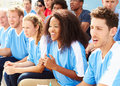 Spectators in team colors watching sports event sitting down Royalty Free Stock Photo