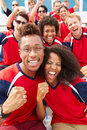Spectators in team colors watching sports event smiling Stock Photography