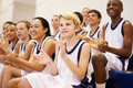 Spectators watching high school basketball team match in gymnasium clapping Royalty Free Stock Images