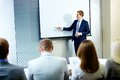 Speech at conference confident businessman pointing whiteboard while making Stock Images