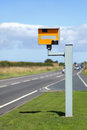 Speed camera uk static with speeding cars approaching on a rural road Royalty Free Stock Photos