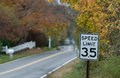 Speed limit autumn a mph sign stands along a suburban street flanked by yellow and orange leaves Royalty Free Stock Photos