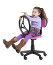 Speed young a girl sitting with a steering wheel Royalty Free Stock Images