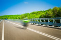 Speeding bike on a straight road motor sunny summer day with green trees the background Royalty Free Stock Photo