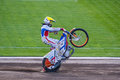 Speedway bike rider doing wheelie on his special motorbike after winning race Royalty Free Stock Photo