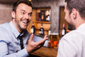 Spending friday night in bar two happy young men shirt and tie talking to each other and gesturing while drinking beer at the Royalty Free Stock Photo