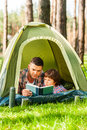 Spending good time outdoors father and son reading book while lying in tent together Royalty Free Stock Photography