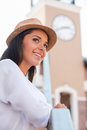 Spending good time outdoors low angle view of beautiful young woman in funky hat looking away and smiling while standing Royalty Free Stock Images