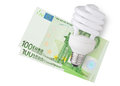 Spending money enegy saver bulb over euro bills on white background Royalty Free Stock Photos