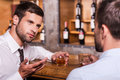 Spending night in bar two confident young men shirt and tie talking to each other and gesturing while drinking whisky at the Stock Images