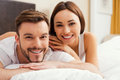 Spending quality time together beautiful young loving couple bonding to each other while lying in bed Royalty Free Stock Photo