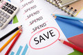 Spending and saving message the word save circled in red below a list of surrounded by pencils graphs books calculator Royalty Free Stock Photo