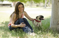Spending some time with her dog young beautiful woman having fun and pug at a park Royalty Free Stock Images