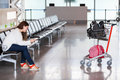 Spending time in airport lounge with luggage hand cart one woman only Royalty Free Stock Image