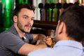 Spending time in bar two young men talking to each while drinking beer Royalty Free Stock Photo