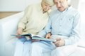 Spending time together portrait of a candid senior couple reading book at leisure Stock Photos