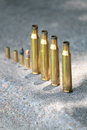 Spent shells rounds lined up on concrete table at an outdoor shooting range Royalty Free Stock Images