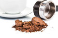 Spent or used coffee grounds with portafilter and a cup of freshly brewed coffee in the background Stock Photo