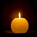 Spherical candle shines on a dark background Stock Images