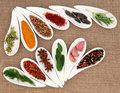 Spice and herb seasoning fresh leaf selection in leaf shaped white dishes over hessian background Stock Photo