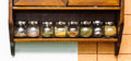 Spice rack different spices with many in clear jars on kitchen wall Royalty Free Stock Photos