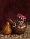 Spiced pears chutney a little jat of pear with a fresh pear standing beside studio shot on a reddish brown backdrop Stock Photos