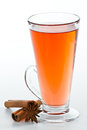 Spiced ted red tea served in a tall glass isolate don a white background with cinnamon sticks and a anise star Royalty Free Stock Image