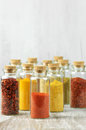 Spices in bottles assorted ground on rustic wood Royalty Free Stock Images